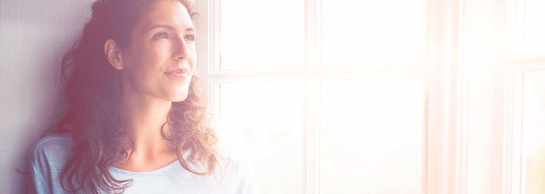 Femme reflechissant lueur orange fenêtre